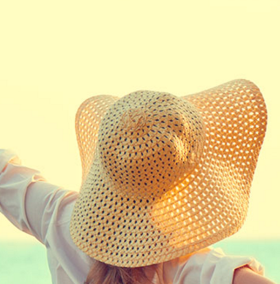 Woman wearing a sun hat facing towards the sun