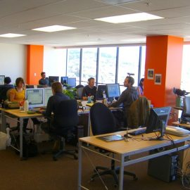 Workers at a marketing agency in an open office space with desks, compters, coffee mugs and supplies